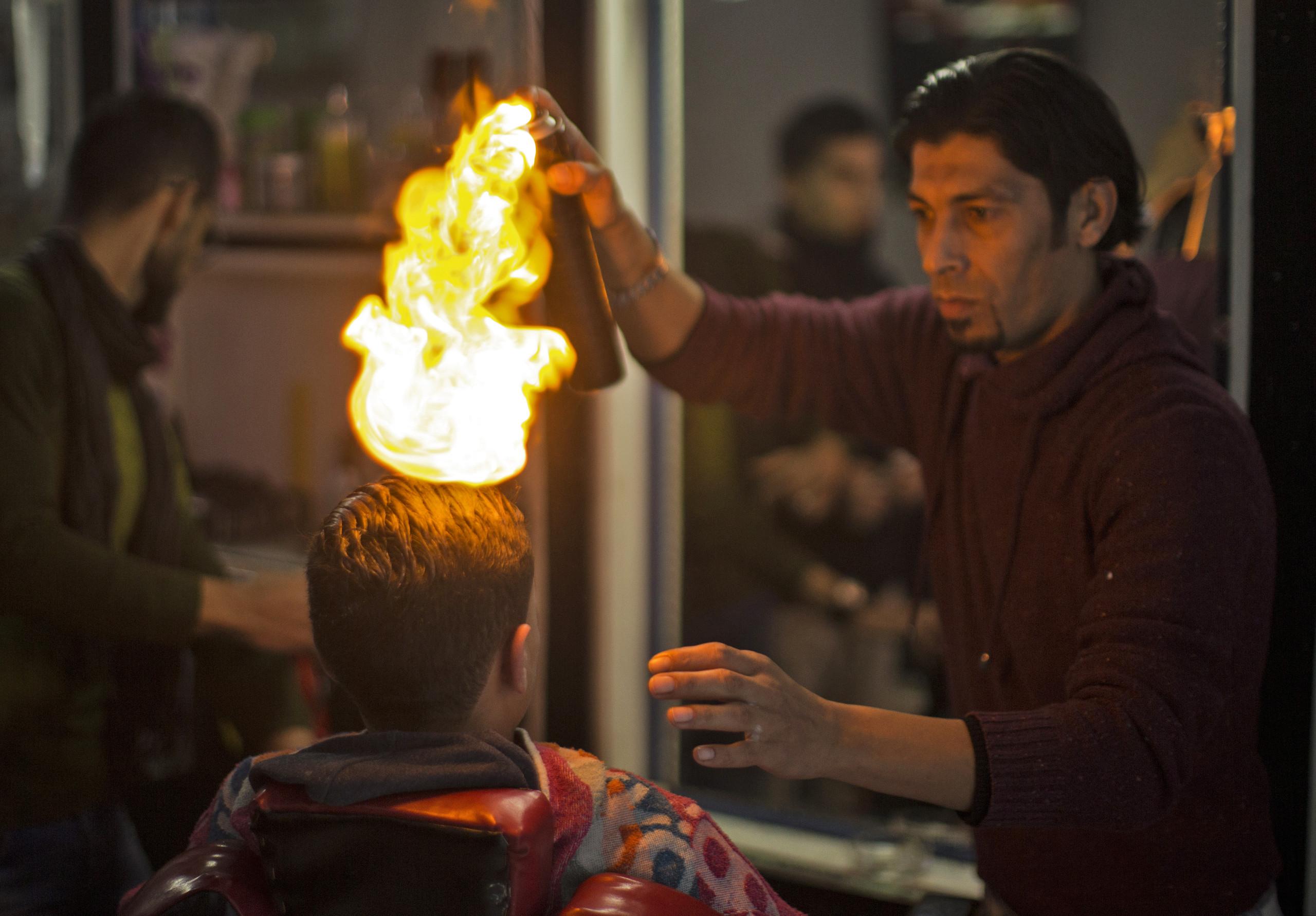 بالصور.. حلاق فلسطيني يستخدم النار فوق رؤوس زبائنه
