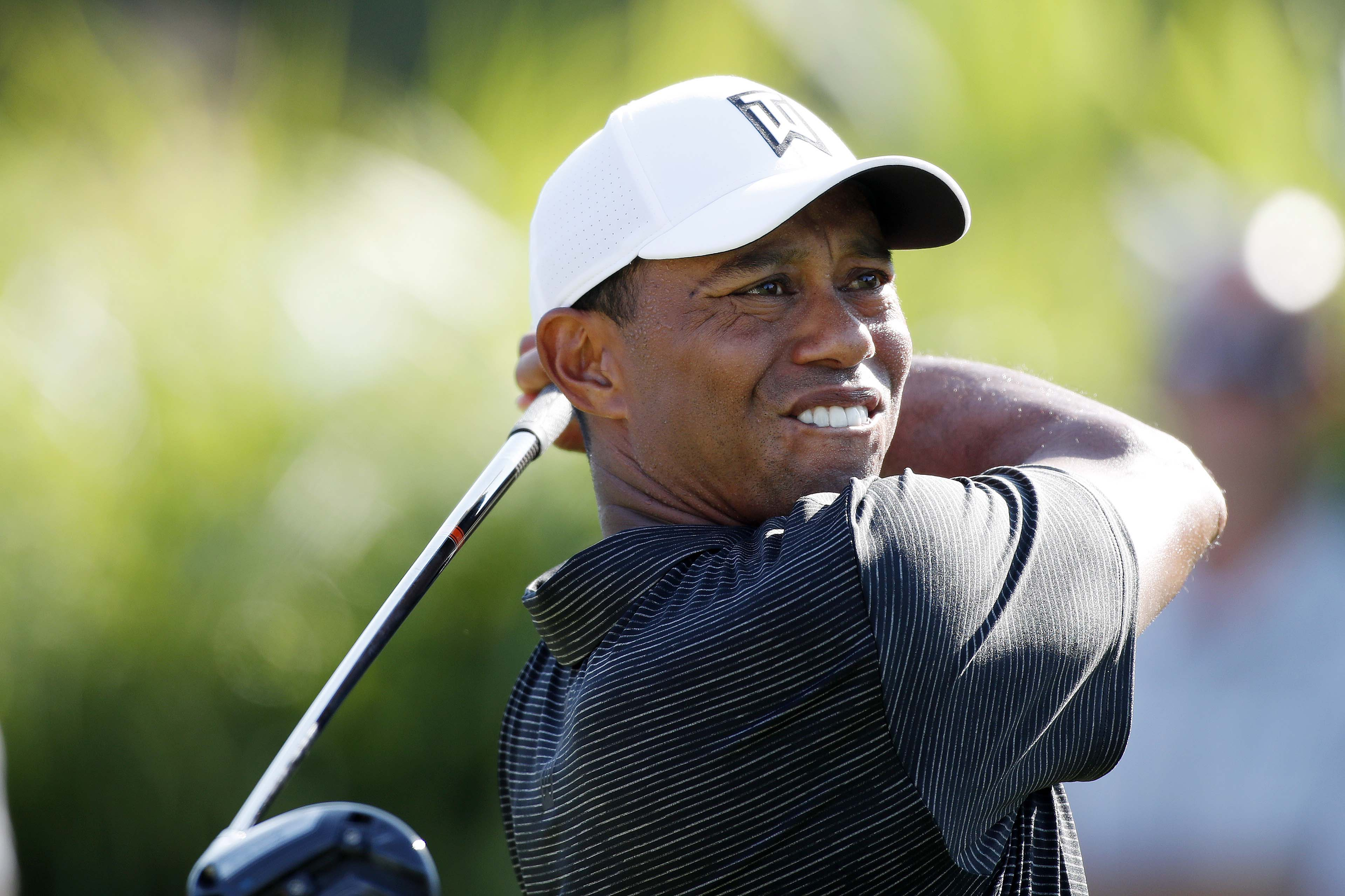 Golf: Woods and McIlroy toil but finish within striking distance