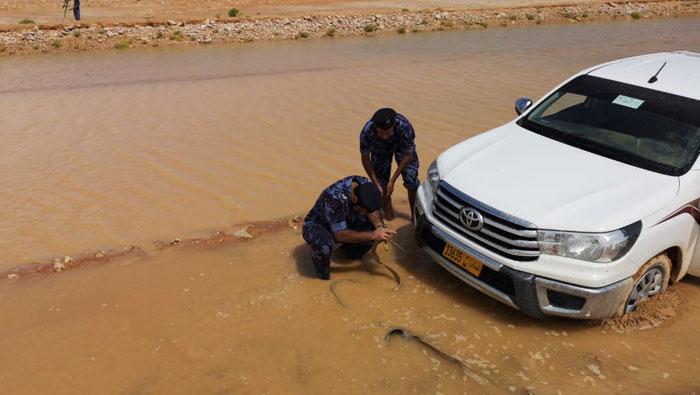 Royal Oman Police help remove car stuck in mud