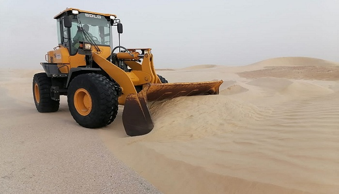 Sand dunes being cleared from roads in Oman